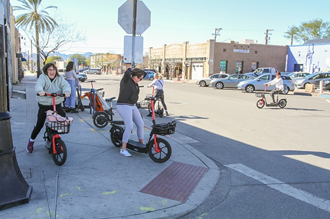 Tourists on Fourth Avenue decide to use scooters to see the Old Pueblo, instead of hoofing it.