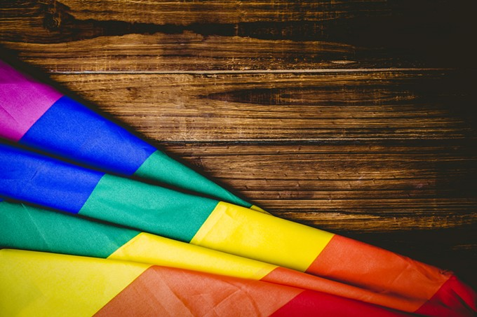 bigstock-gay-pride-flag-on-wooden-table-85889147.jpg
