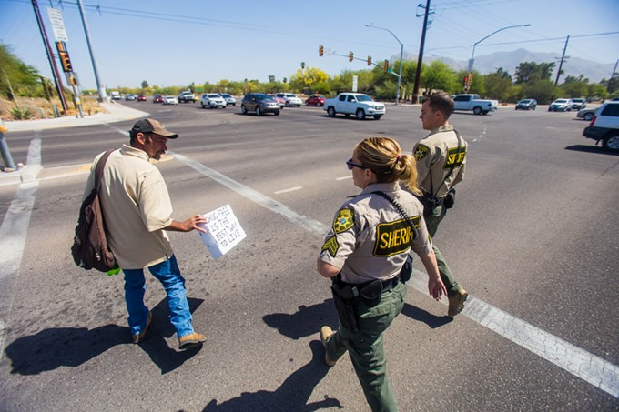 A panhandler, left, is escorted across the street by Pima County Sheriff's Deputy Daniel Sharp Jr., and Sgt. Erin Gibson, after talking about the potential new signs that may prohibit individuals from standing in medians in unincorporated areas of Pima County.