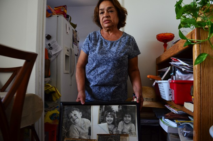 Cecilia with old photos of her children—some of the few possessions she could rescue from her home.