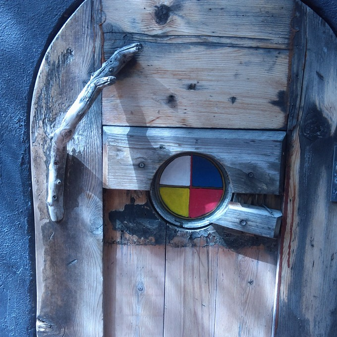 The outer side of the sweat lodge door with its hand-painted glass medicine wheel.