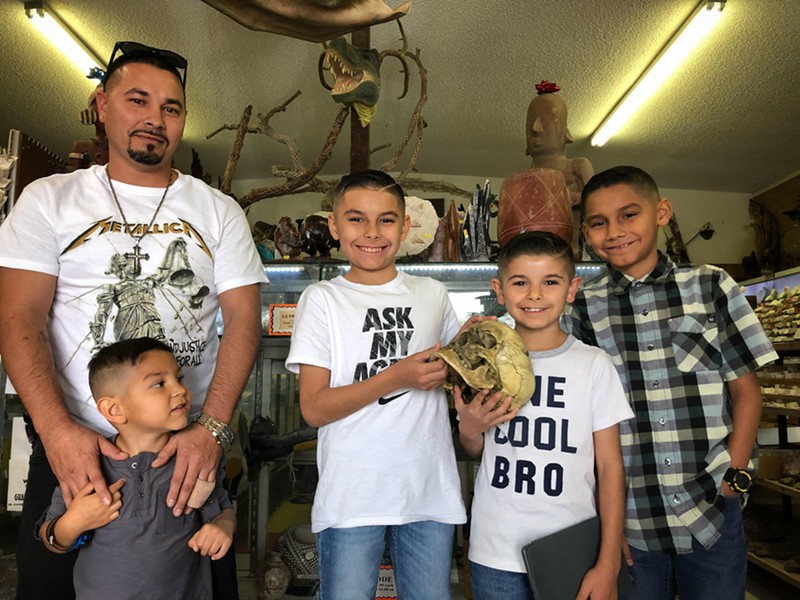 Hector Espinoza, his four sons and a human skull at the Tucson Mineral & Gem World. - BRIAN SMITH