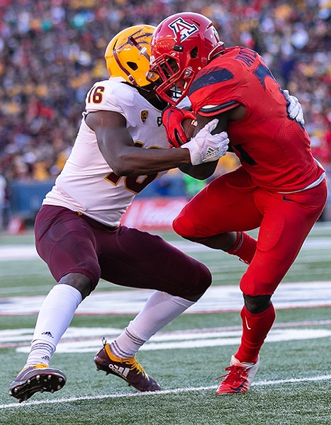 Arizona's J.J. Taylor, right, tries to spin away from Arizona State's Ashari Crosswell. - PHOTOS BY SIMON ASHER