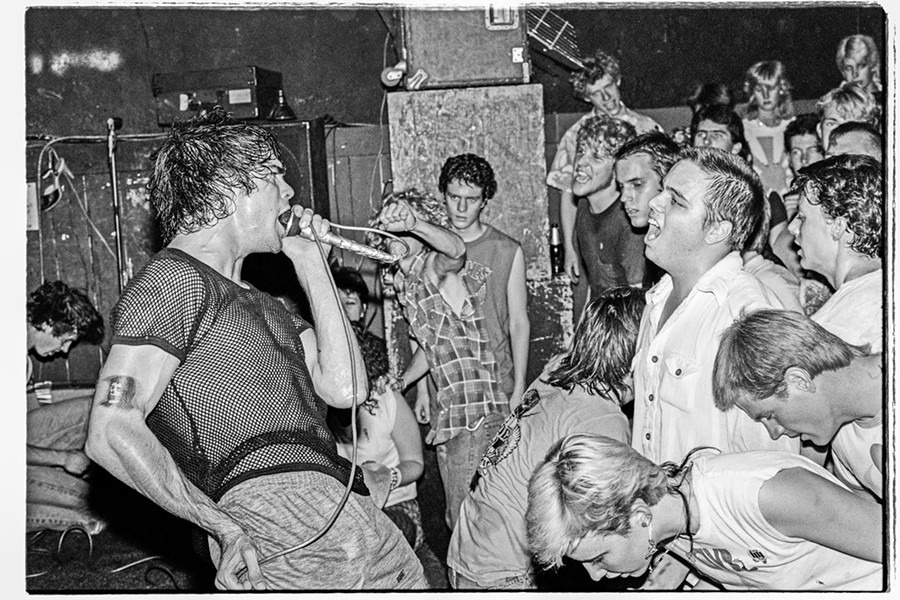 """""""Black Flag at The Backstage on 4th Ave., May 13, 1983. I got on stage next to Greg Ginn soon after they started playing because I knew taking photos in front of the stage would have been difficult with the crowd movement. Luckily no one kicked me off stage."""" - ED ARNAUD"""