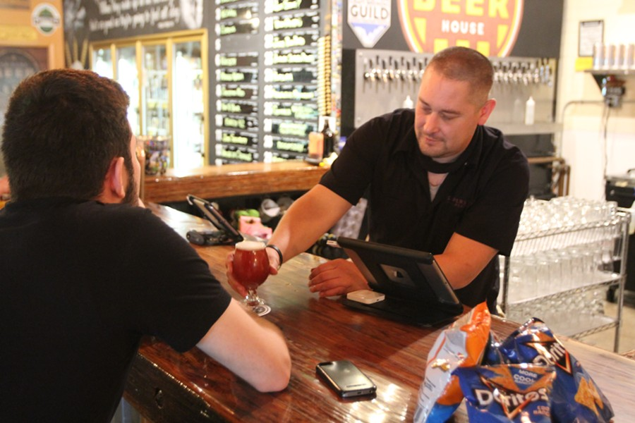 Arizona Beer House bartender Greg Turkington serves a brew to Ben McBride two minutes after midnight on Monday, May 11 after Gov. Doug Ducey announced restaurants - and by extension, bars -  could reopen dine-in service on May 4, 2020. - AUSTIN COUNTS
