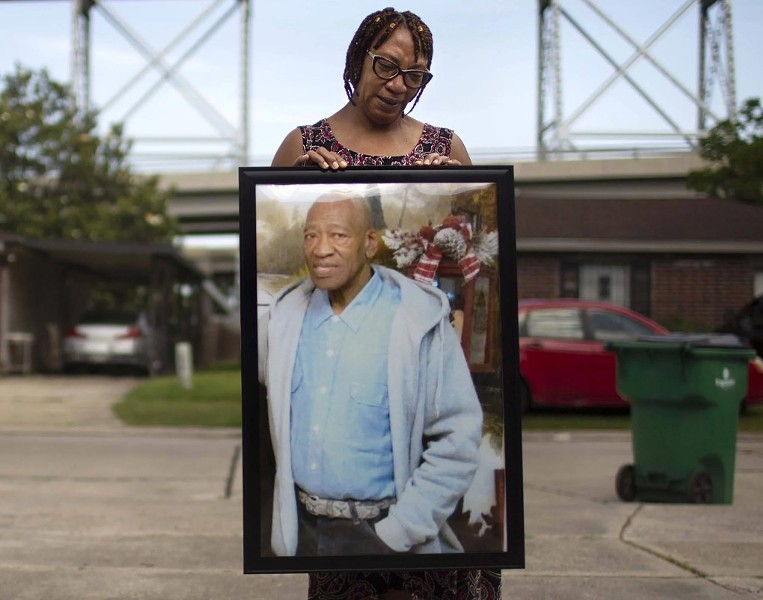 Terry Rogers holds a photo of Michael Williams, her brother, in front of her home in Bridge City, Louisiana, on May 17, 2020. (Kathleen Flynn/ProPublica)