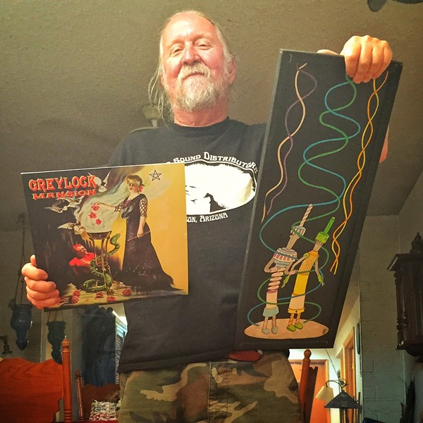"Steve Purdy with his Greylock Mansion album cover and a trash-art piece he calls ""The Transmission People."""
