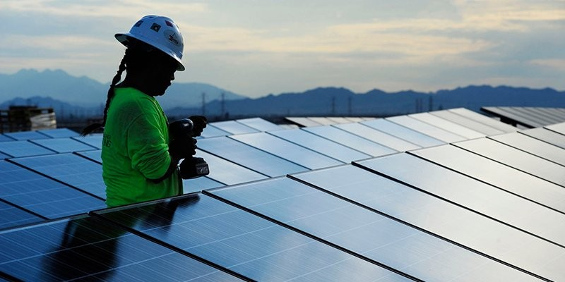 Daniel Baldonado, a contract worker for a steel fabrication company, Ironco Enterprises, installs a series of solar panels on the roof of Wells Fargo Arena on Arizona State University's Tempe campus. The installation is just one of dozens of solar panels that have been installed on roofs of ASU's parking structures and buildings.