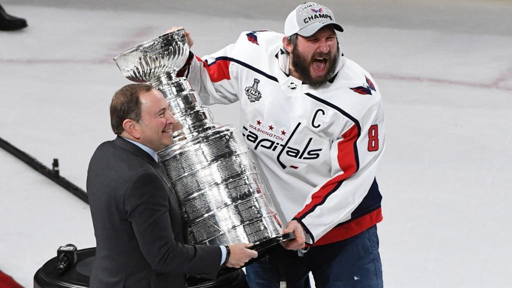 15c4031a4 click to enlarge Washington Capitals captain Alex Ovechkin, right, grasps  the Stanley Cup trophy from Commissioner Gary