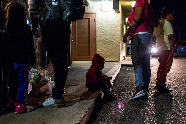 A young boy sits on the curb at a Tucson motel where 112 migrants, most from Guatemala, temporarily stayed while seeking asylum. Churches, community organizations and others donated money and supplies to house and feed families before they were sent to stay with relatives across the country. - PHOTO BY NICOLE NERI/CRONKITE NEWS