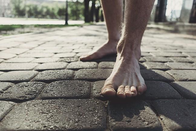 bigstock-man-bare-feet-stepping-on-pave-244512781.jpg