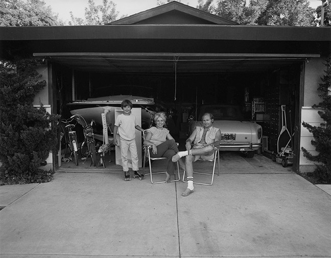 Our house is built with the living room on the back, so in the evenings we sit out front of the garage and watch the traffic go by, from Suburbia, 1972 gelatin silver print, © Bill Owens, courtesy Etherton Gallery