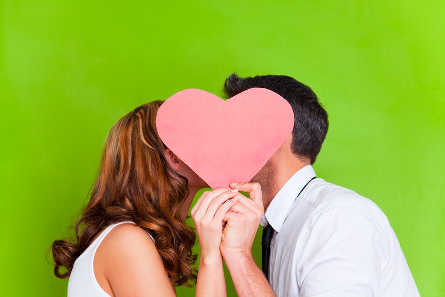 bigstock-young-couple-kissing-behind-pr-19421999.jpg