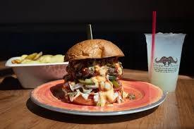 Divine Bovine's Burger topped with lettuce tomato dill pickle and Divine sauce - DIVINE BOVINE