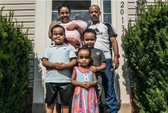 Gebrish Weldemariam, who was laid off by an airline catering company that later received government aid, with his family outside their Virginia home. (Dee Dwyer for ProPublica)