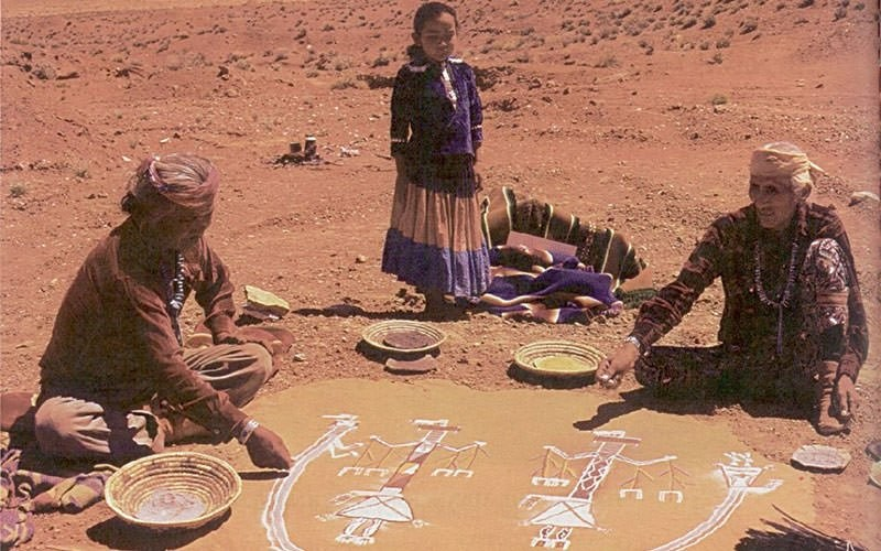 A young patient watches a medicine man, right, and helper prepare a sandpainting as part of her healing ceremony in 1980. - PHOTO COURTESY OF THE NATIONAL LIBRARY OF MEDICINE, NAVAJO AREA INDIAN HEALTH SERVICE TODAY, IHS