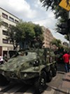 A tank makes it way through downtown Mexico City after a parade.